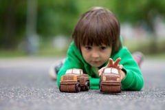 Funny little boy playing with car of chocolate, outdoor Stock Photography