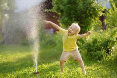 Funny little boy playing with garden sprinkler in sunny backyard royalty free stock photo