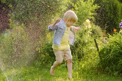 Funny little boy playing with garden sprinkler in sunny backyard. Preschooler child having fun with spray of water. Summer outdoors activity for kids royalty free stock image