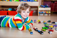 Funny little boy playing with lots of toy cars indoor Royalty Free Stock Photography