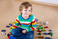 Funny little boy playing with lots of toy cars indoor Stock Images