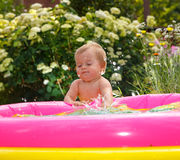 Funny little boy playing with water in baby pool Royalty Free Stock Photos