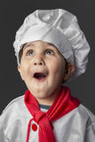 Funny, little boy preparing healthy food on kitchen over grey ba Royalty Free Stock Photography