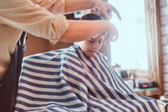 Funny little boy is getting trendy haircut from expirienced barber at fashionable hairdressing salon at firs time. Funny little boy is preparing for the school stock photo
