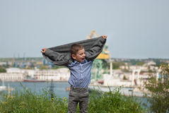 Funny little boy raised his hands up with his jacket Royalty Free Stock Photos