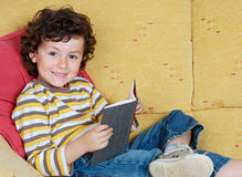 Funny little boy reading a book on the sofa. Funny little boy reading a book lying on the sofa Stock Photos