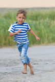 Funny little boy running outdoors Royalty Free Stock Photos