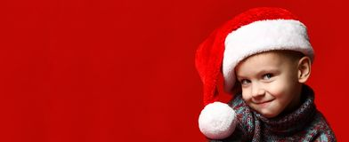 Funny smiling joyful child boy in Santa red hat stock images
