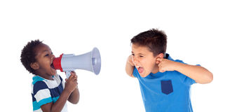 Funny little boy shouting through a megaphone to his friend. Stock Images
