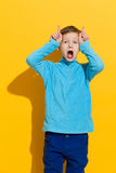 Funny little boy showing antlers Stock Photo