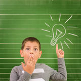 Funny little boy showing on the board: light bulb Royalty Free Stock Photography