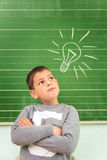 Funny little boy showing on the board: light bulb Royalty Free Stock Images
