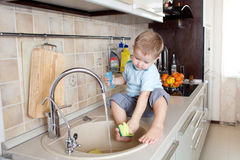 Funny little boy sitting on kitchen table. Cute little boy sitting on kitchen table Royalty Free Stock Photo