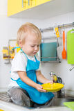 Funny little boy sitting on kitchen table and washing dish Stock Photo