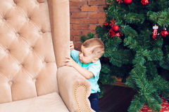 Funny little boy standing near sofa and Christmas tree with colorful xmas ball Stock Photography