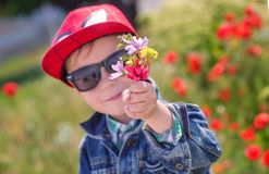 Funny little boy in sunglasses with a bouquet Stock Photo