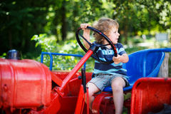 Funny little boy of three years playing on tractor Royalty Free Stock Photography