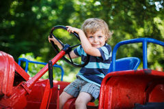Funny little boy of three years playing on tractor Royalty Free Stock Photos