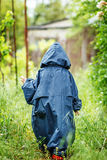 Funny little boy walks in the rain in a raincoat with a hood. Royalty Free Stock Images