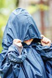Funny little boy walks in the rain in a raincoat with a hood Royalty Free Stock Photography