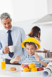Funny little boy wearing hardhat during breakfast with his paren Stock Photos