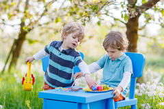 Funny little boys playinig and painting colorful eggs Stock Images