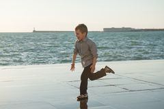 Funny little caucasian kid running along sea shore in port town outdoor Stock Photos