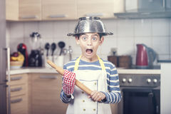Funny little chef. Funny little boy chef with pasta drainer in the head grimacing with open mouth Royalty Free Stock Images