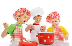 Funny little chefs. Three little chefs enjoying in the kitchen Stock Photos