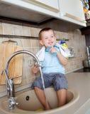 Funny little child boy washing dish on kitchen Stock Photos