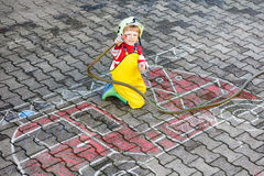Funny little child of four years having fun with fire truck pict. Creative leisure for kids: Funny little child of four years having fun with fire truck picture Stock Photos