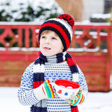 Funny little child holding big cup with snowflakes and hot choco Stock Photos