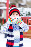 Funny little child holding big cup with snowflakes and hot choco Royalty Free Stock Photography