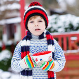 Funny little child holding big cup with snowflakes and hot choco Royalty Free Stock Images