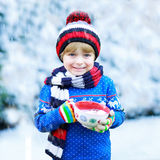 Funny little child holding big cup with snowflakes and hot cocoa Stock Photo