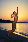 Funny little child jumping on beach at sunset. Stock Photography