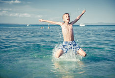 Funny little child playing in the sea splashing water and jumping Stock Photography