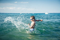 Funny little child playing in the sea splashing water laughing Stock Photos