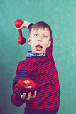 Funny little child with red dumbbell and apple Royalty Free Stock Image