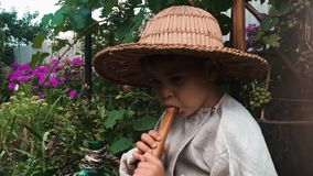 Funny little child in straw hat trying to play on flute with green garden on background. Happy boy playing on music instrument stock video