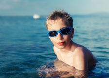 Funny little child with sunglasses swimming in the sea. Stock Photography