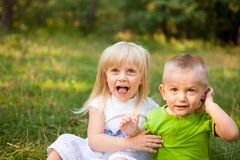 Funny little children - blonde little girl and boy sitting together. With copy space Stock Image