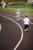 Little children playing on stadium stock images