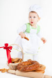 Funny little cook. Little baby girl in the cook costume standing near bread rolls and bagels. She is looks surprised Royalty Free Stock Photo