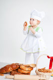 Funny little cook. Little baby girl in the cook costume standing near bread rolls and bagels. She is eating bagel Royalty Free Stock Images