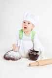 Funny little cook. Little baby girl in the cook costume sitting near bread and pot of flour Stock Images