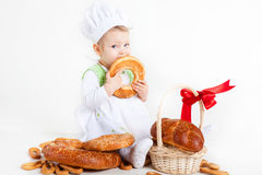 Funny little cook. Little baby girl in the cook costume sitting near bread rolls and bagels. She is eating bagel Stock Images