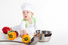 Funny little cook. Little baby girl in the cook costume sitting near pan and vegetables Stock Photography