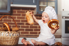 Funny little cook in kitchen with bakery. Basket with loafs a bread and bagels Royalty Free Stock Photos