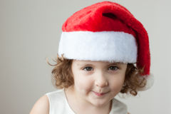 Funny little curly blonde girl in a Santa hat Royalty Free Stock Photo
